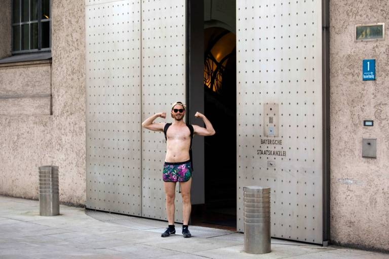 A man who is wearing swimming trunks is standing in front of the entrance of the Bayerische Staatskanzlei in Munich.