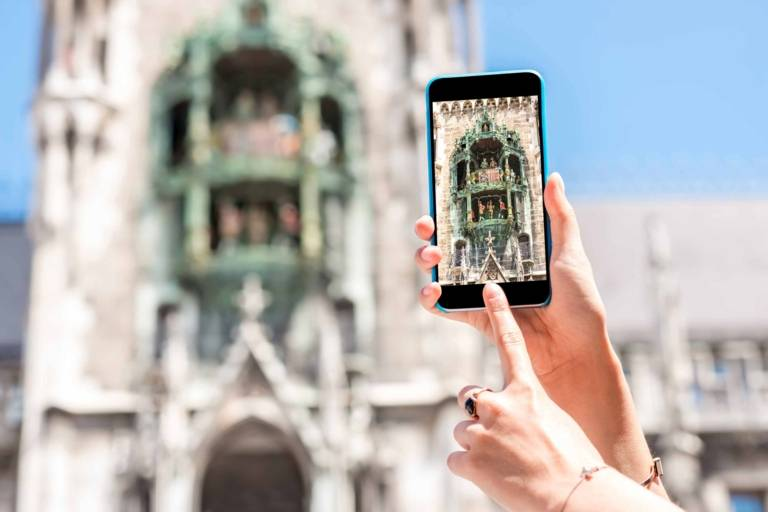 A woman is taking a picture of the Glockenspiel at Neues Rathaus in Munich.