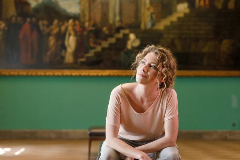 A woman with curly hair is sitting in front of a painting at Sammlung Schack in Munich.