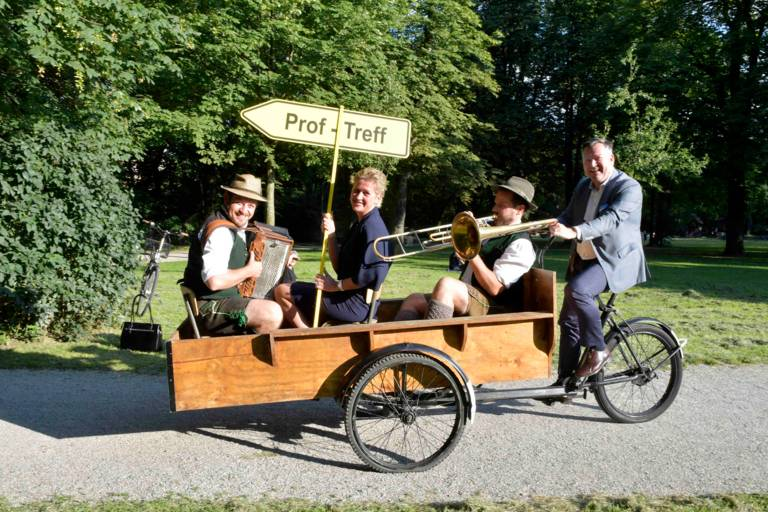 MCA Chairwoman Andrea Bisping and two musicians are cycled by Mayor Josef Schmid to the ProfTreff in Munich.