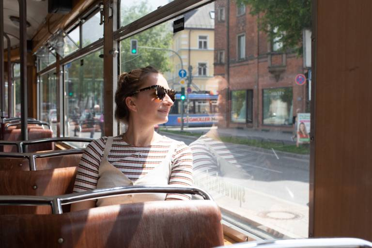 Young woman sitting at a window in a tram in Munich.