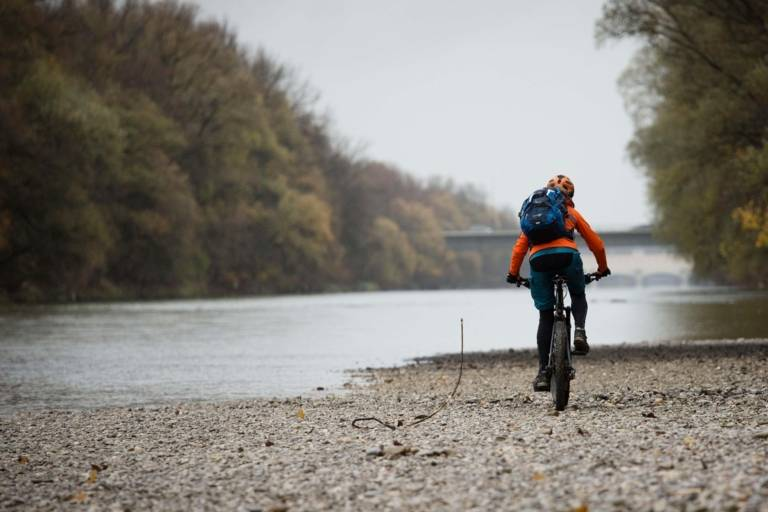 A woman is riding a mountain bike along the Isar River.