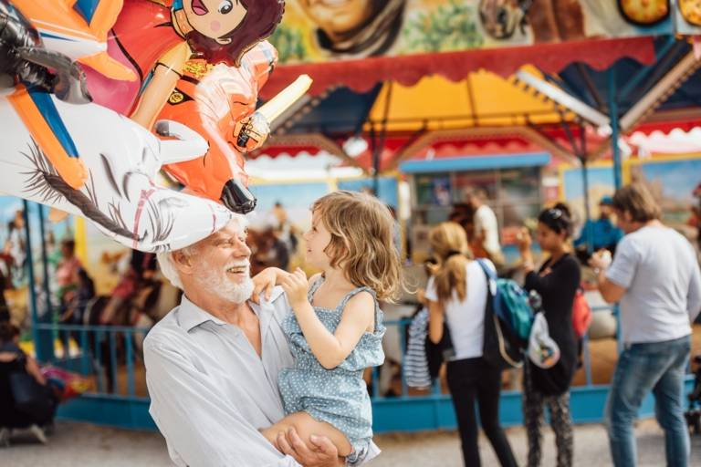 A grandfather is carrying his granddaughter in his arms at the Auer Dult in Munich.