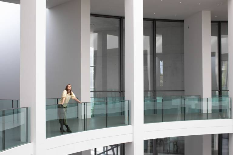 A young woman is standing in an empty museum in Munich.