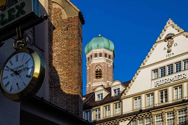 Pedestrian zone in Munich with one of the two towers of the Frauenkirche in Munich.