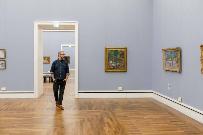 A man with glasses and beard is going through the Neue Pinakothek in Munich and is looking at the paintings.