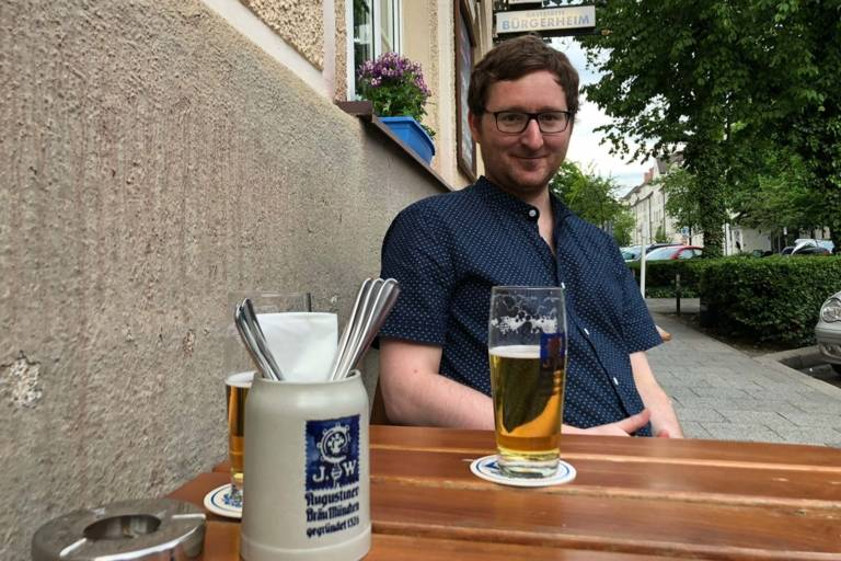Man with beer in front of a restaurant in Munich.
