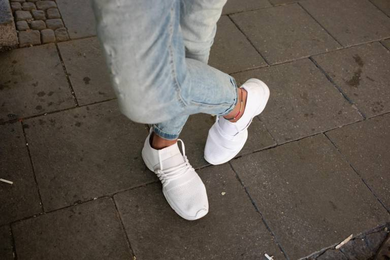 A man's jeans and white sneakers in Munich.