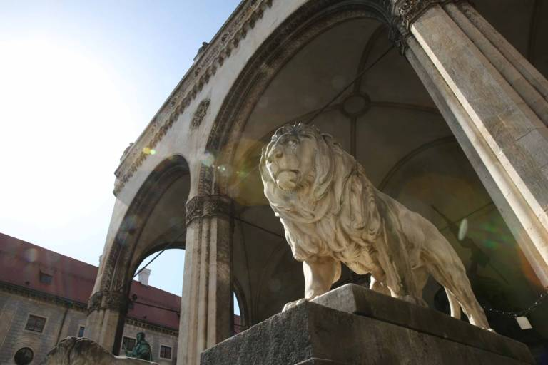Statue of a marble lion flanking the steps of the Feldherrnhalle at Odeonsplatz in Munich.