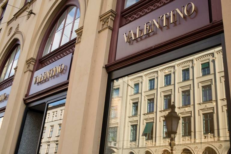 View of house facades at Maximilianstraße in Munich reflected in the shop window of Valentino.