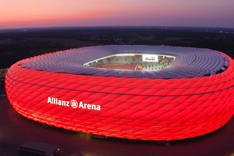 Allianz Arena illuminated in red at night.