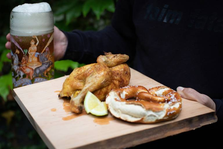 A crispy chicken with pretzel and lemon on a wooden plate in Munich