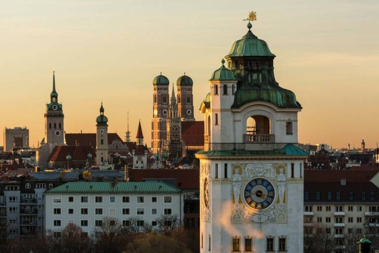 Panoramic view of the inner city of Munich at sunset with the Müllersches Volksbad in front and the towers of Alter Peter, Heilig-Geist-Kirche and Frauenkirche in the background.