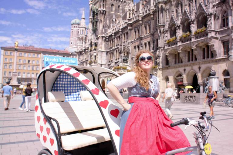A woman in a dirndl leans against a rickshaw decorated with hearts on Munich's Marienplatz.