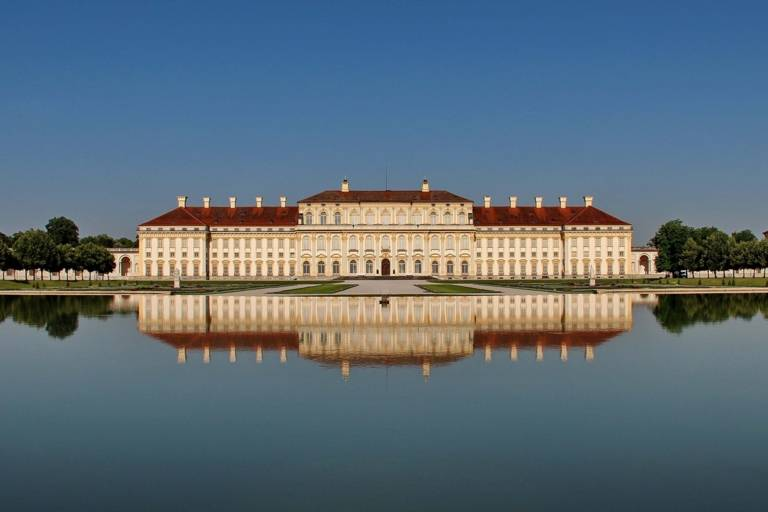 The silhouette of Schleissheim Palace is reflected in the water of the canal.