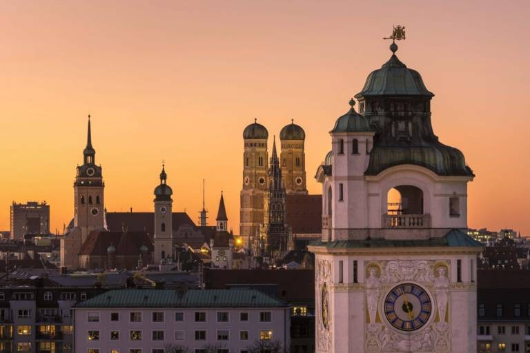 Panoramic view of the inner city of Munich at sunset with the Müllersches Volksbad in front and the towers of the Alter Peter, Heilig-Geist-Kirche and Frauenkirche in the background.